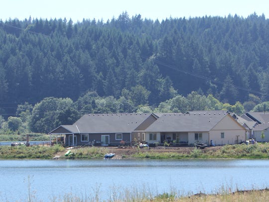 Paddle boats sit behind houses on the banks of North