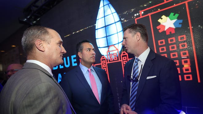 El Paso City Manager Tommy Gonzalez, center, talks with Housing Authority of the City of El Paso CEO Gerald Cichon, right, and Cary Westin, deputy city manager of economic development and tourism during a recent ceremony to symbolically reignite the blue flame on a Downtown building.