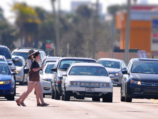 Two women walk across State Road A1A at Shepard Drive in Cocoa Beach.