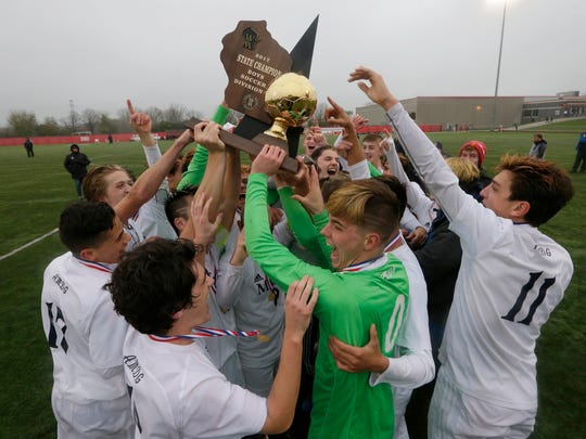 Marquette celebrates after winning the WIAA Division 1 boys state soccer championship over Arrowhead.