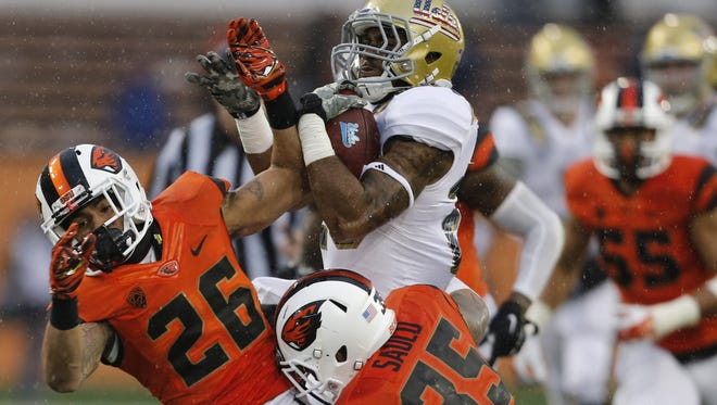 UCLA's Nate Starks, center, runs through Oregon State's Devin Chappell, left, and Caleb Saulo in the second half of an NCAA football game, in Corvallis, Ore., on Saturday, Nov. 7, 2015. UCLA won 41-0. (AP Photo/Timothy J. Gonzalez)