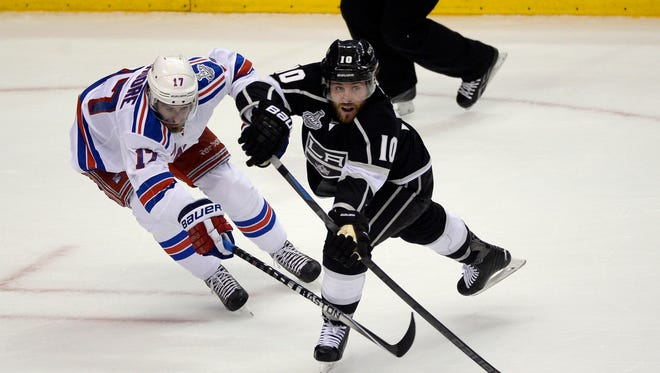 Rangers defenseman John Moore, who returned Saturday after serving a two-game suspension, chases Los Angeles Kings center Mike Richards, right, in the first period of Game 2.