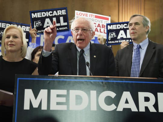 Sen. Bernie Sanders, I-Vt., joined by, Sen . Kirsten Gillibrand, D-N.Y., left, and Sen. Jeff Merkley, D-Ore., front right, introduces the Medicare for All Act of 2019, on Capitol Hill in Washington, Wednesday, April 10, 2019.