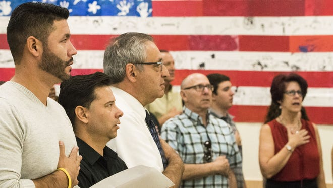 Shortly after 56 immigrants from 23 countries raised their right hands and pledged an oath of allegiance to the United States, the lights dimmed and a video of President Donald Trump appeared on two screens at the front of the room of the U.S. Citizenship and Immigration Services office in Phoenix on Tuesday, Oct. 24, 2017.