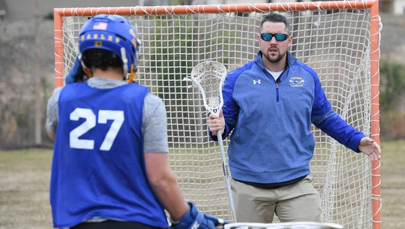 Eastside lacrosse coach Mike McCallan works with goalie Jamison Lowry during the teams practice on Monday, March 26, 2018. McCallan is back coaching after having brain surgery to remove a benign tumor behind his optic nerve.