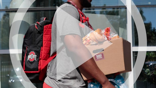 In this file photo Ohio State Buckeyes offensive lineman Thayer Munford carries a box of food and drinks as he leaves following a voluntary workout on Monday, June 8, 2020 at the Woody Hayes Athletic Center in Columbus, Ohio. Due to the ongoing COVID-19 pandemic, players are socially distanced during workouts and only arrive and leave in small groups.