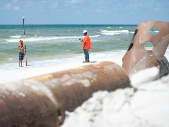 From left, Russell Littleton and Juel Tillman survey progress on the Pensacola Beach renourishment project as it reaches the halfway mark July 28, 2016.