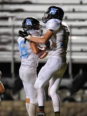 Union County's Dalton French is congratulated by teammate Logan Thomas after scoring a touchdown during last year's game at Madisonville.