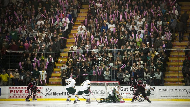 Students cheer as Catamounts goalie Mike Santaguida (1) makes a save during the men's hockey game between the Northeastern Huskies and the Vermont Catamounts at Gutterson Fieldhouse on Friday night.