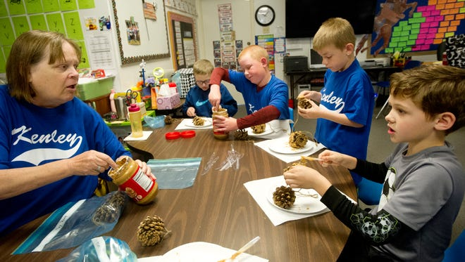 Lynn Reed helps second- and third-graders at Kenley School make pine cone bird feeders Friday as part of Earth Day celebrations.