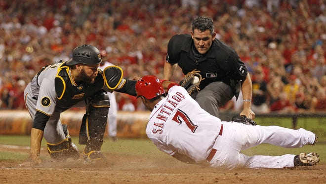 The Reds' Ramon Santiago is tagged out at the plate by Pirates catcher Russell Martin on July 12.