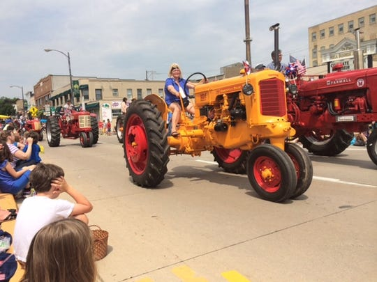 Farm tractors roll on Main Avenue in downtown De Pere toward the Claude Allouez Bridge during the 2014 De Pere Kiwanis Memorial Day Parade.