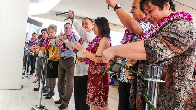 President and CEO Alfredo Bengzon, center, raises a section of a woven rope into the air, during a ribbon cutting ceremony with Gov. Eddie Calvo and other dignitaries at the Guam Regional Medical City in Dededo on Monday, July 20.