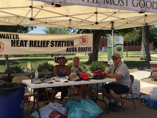 Volunteers Chanel Tanner, Lisa Kelly and Steve Santos hand out water at a Salvation Army hydration station in Phoenix.
