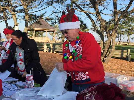 Mark Speaker, member of the Lavallette Business Association, helps a runner register for the Ugly Lavallette Christmas Sweater Run on Dec. 5.