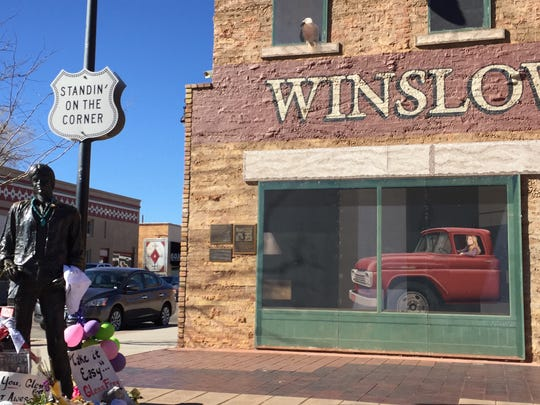 A statue of Jackson Browne surrounded by tributes to the late Glenn Frey, with whom he wrote the song that made a street corner in Winslow, AZ, famous.