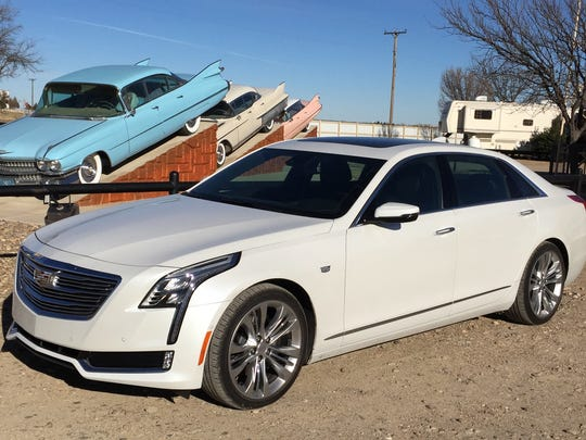The 2016 Cadillac CT6 parked by vintage Caddies at  Cadillac Ranch RV Park in Amarillo, Texas.