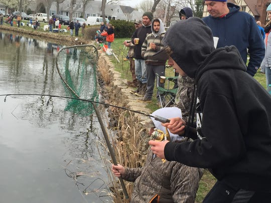 Jack Bycsek reels in a rainbow trout at Spring Lake. His dad Dave Bycsek (right) stands in the water to with the net on April 9, 2015.