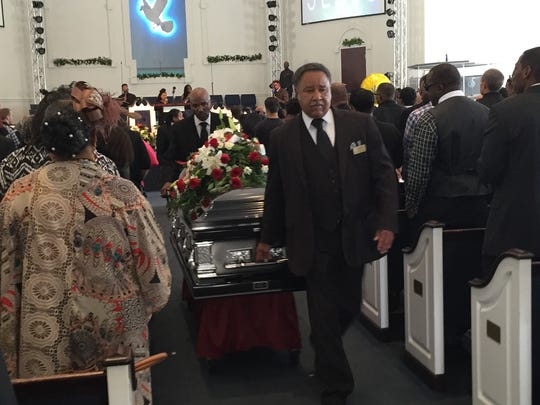 Funeral officials carry the casket of Josh Artis after