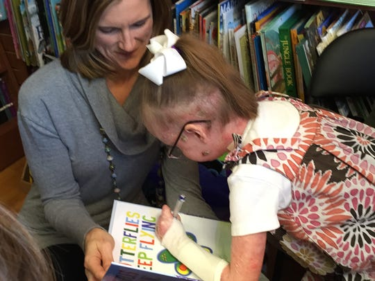 "Ella Murray signs a copy of ""Butterflies Keep Flying"""