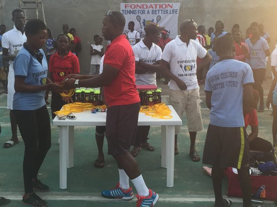 Paul Segodo distributes equipment during a visit last summer to his native country of Benin, Africa, through his Tennis for a Better Life Foundation.