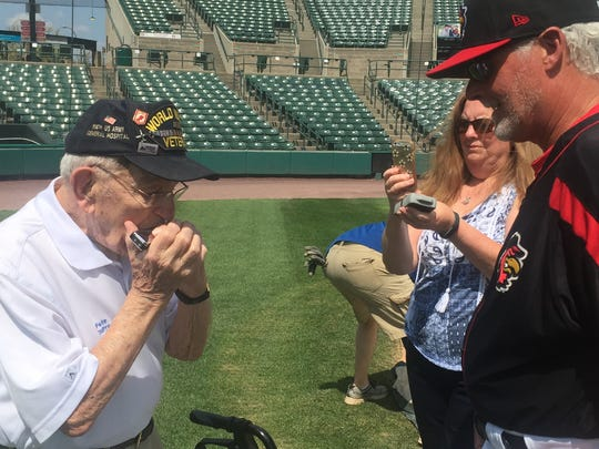 """Pete DuPre, 94, who has gained fame for his harmonica playing at military and sporting events, plays """"Take Me Out to the Ball Game'' for Red Wings pitching coach Stu Cliburn. """"You pitch half as good as that, Pete, you'll be just fine,'' Cliburn said."""