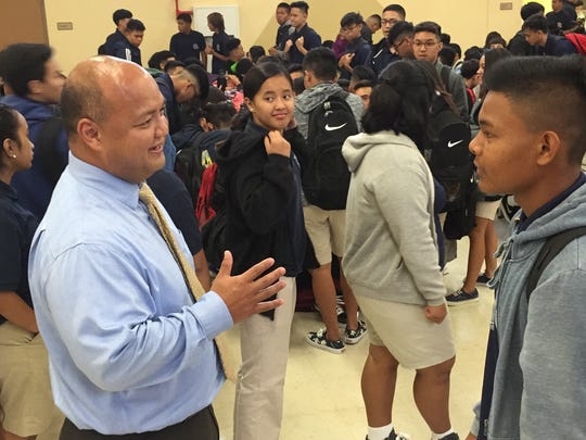 In this file photo, Guam DOE Superintendent Jon Fernandez talks to a student at Okkodo High School.