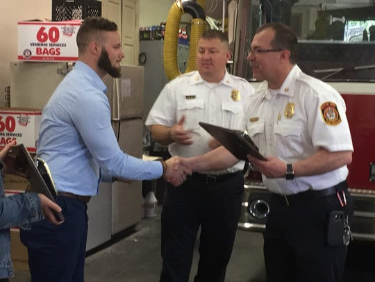 Compton and Wahl are shown here presenting the plaques to Chad Deardorff, deputy fire chief, and David Michaels, fire chief.
