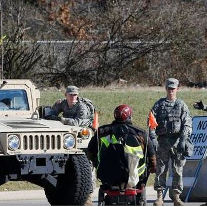 A man in a wheelchair speaks to the National Guard