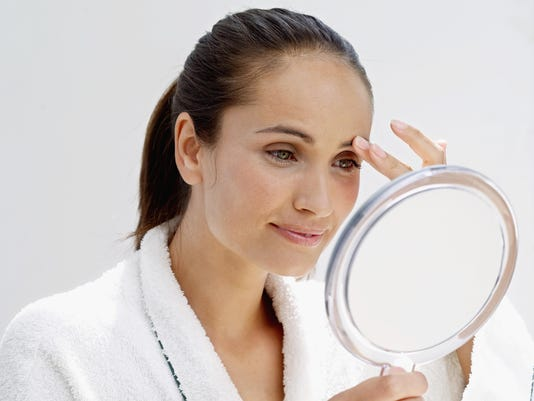 Young woman looking in mirror and touching eyebrows