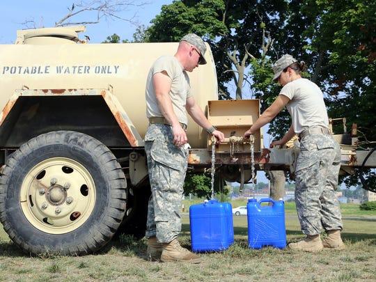 Specialists Rueben Miller, 35, of Mount Vernon, Ohio, left, and Megan Parks, 23, of Columbus, Ohio, fill water jugs for resident Caren Mohn of Northwood, Ohio.