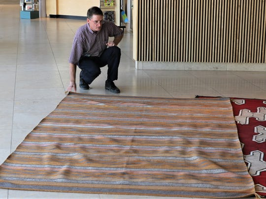 Farmington Museum Director Bart Wilsey takes a closer look at a large crystal-pattern rug that will be featured in Saturday's Navajo Rug Benefit Auction.