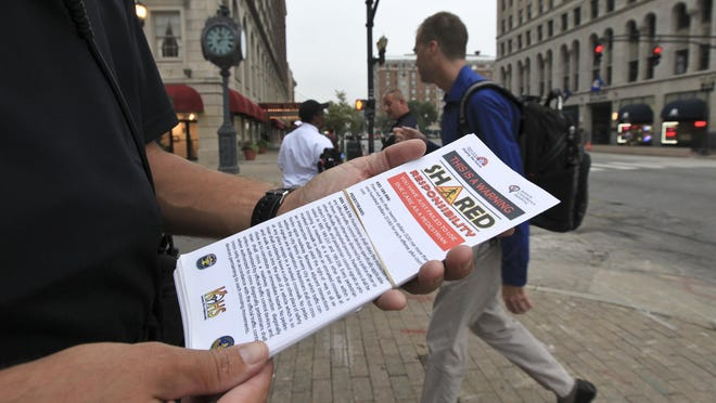 Members of the LMPD Traffic Unit handed out warnings at the intersection of Fourth Street and Broadway Tuesday morning.
