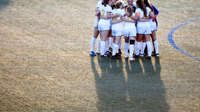 The University of Vermont women's soccer team huddles before its game against Sacred Heart on Friday night at Virtue Field. UVM won, 2-1. The team lost to Rhode Island on Sunday.