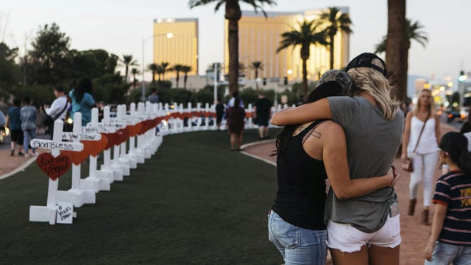 """Women comfort each other at a memorial in Las Vegas. Each of 58 crosses has the name of a victim killed during the mass shooting at the Route 91 Harvest country music festival Oct.1. Mikayla Whitmore/Las Vegas Sun via AP FILE - In this Thursday, Oct. 5, 2017, file photo, a memorial displaying 58 crosses by Greg Zanis stands at the """"Welcome To Las Vegas Sign"""" in Las Vegas. Each cross has the name of a victim killed during the mass shooting at the Route 91 Harvest country music festival this past Sunday, Oct. 1. (Mikayla Whitmore/Las Vegas Sun via AP, File)"""