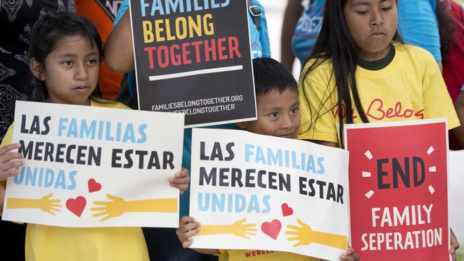In this June 1, 2018, file photo, children hold signs during a demonstration in front of the Immigration and Customs Enforcement offices in Miramar, Florida.
