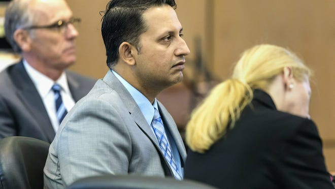 Nouman Raja sits between defense attorney Scott Richardson, left, and paralegal Debi Stratton as attorney Richard Lubin gives his closing arguments in Raja's trial, March 6, 2019 in West Palm Beach, Fla. Raja, a former Palm Beach Gardens police officer, is charged with the fatal 2015 shooting of stranded motorist Corey Jones.