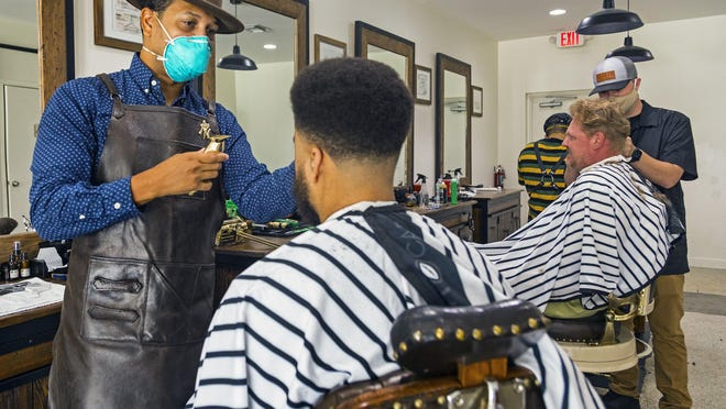 Juan Abreu, owner of the El Cid Barbershop in West Palm Beach, cuts the hair of regular customer Cameron Stone on Monday. Salons and barbershops throughout the county have reopened after being closed in March amid coronavirus concerns.
