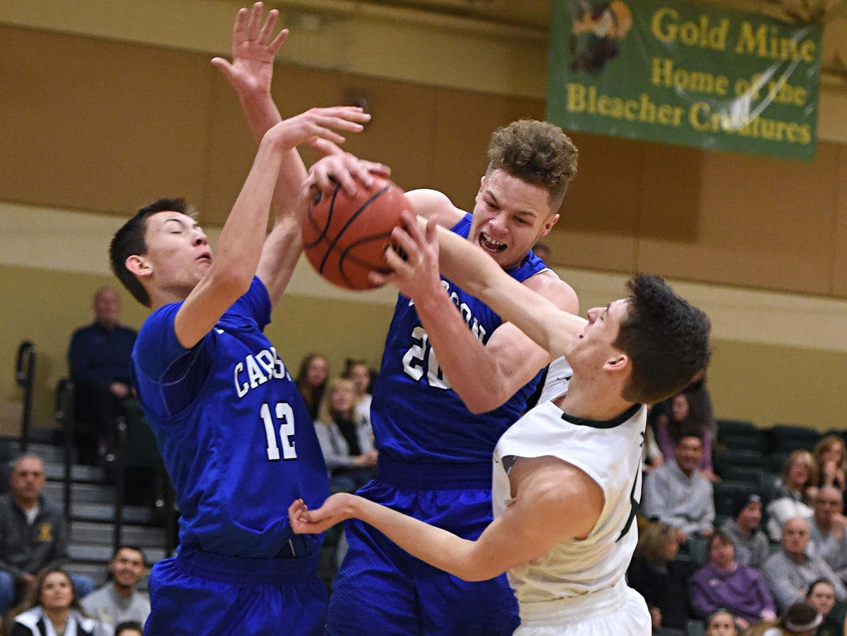 Carson's Tez Allen grabs a rebound between teammate Trenten Robison, left, and Manogue's Aidan Cantwell during the first half of Tuesday's game at Bishop Manogue.