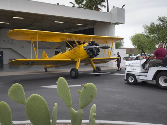 A Stearman PT-17 is towed into Ross Aviation at Scottsdale