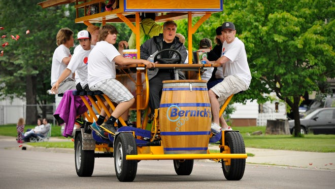 Riders on a party bike throw candy during a parade in Waite Park, Minnesota, in this USA TODAY NETWORK file photo.
