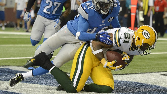 Green Bay Packers tight end Andrew Quarless (81) pulls in a catch for a touchdown against the Detroit Lions safety Isa Abdul-Quddus (42) during Sunday's game at Ford Field in Detroit. Evan Siegle/Press-Gazette Media/@PGevansiegle