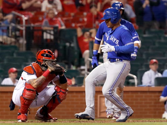 Toronto Blue Jays' Marcus Stroman, right, scores past St. Louis Cardinals catcher Yadier Molina during the 11th inning of a baseball game Tuesday, April 25, 2017, in St. Louis. (AP Photo/Jeff Roberson)