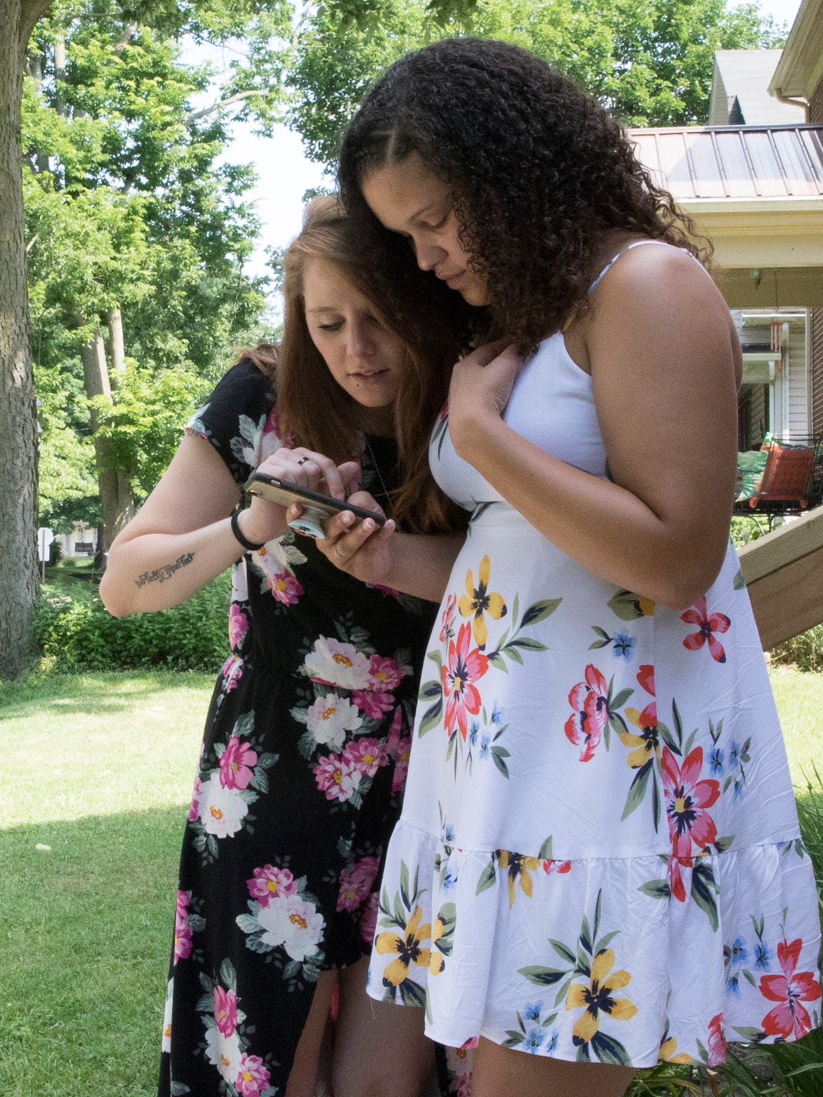 Ashley Mullins, left, looks at pictures with Katie