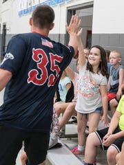 Cameron Delp gives Dan McCauley a high five as the Chillicothe Paints arrive at the Ross County YMCA as part of their community outreach program.