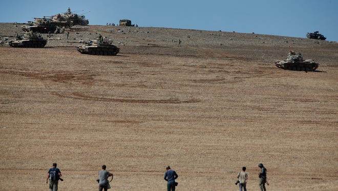 Press photographers walk to take pictures of Turkish tanks holding their positions on a hilltop in the outskirts of Suruc, at the Turkey-Syria border, overlooking Kobani in Syria where fighting had intensified between Syrian Kurds and the militants of Islamic State group Oct. 6.