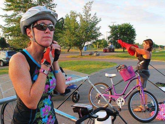 Tara Johns puts on her bike helmet after completing