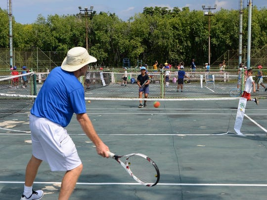 Jake Agna plays tennis with a Cuban kid on the courts of the National Tennis Center in Havana in October 2015.