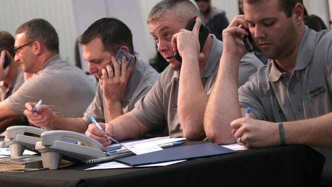 Volunteers from Phillips Tube Group answer phones during the Catalyst Rehab Telethon at the Richland Mall on Saturday.