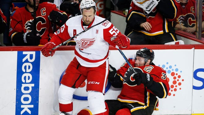 Red Wings defenseman Niklas Kronwall, left, knocks the Flames' Troy Brouwer to the ice during the Wings' 3-2 overtime loss Friday in Calgary, Alberta.